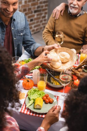 Selective focus of man looking at african american woman holding bun on thanksgiving