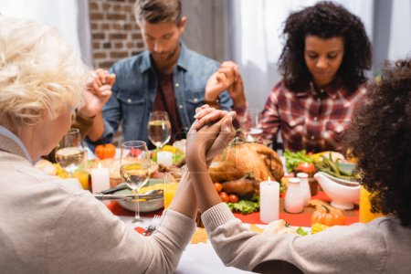 selective focus of multiethnic family with closed eyes holding hands on thanksgiving holiday
