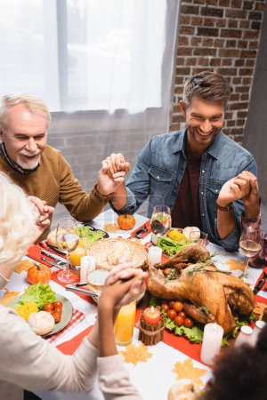 joyful multicultural family holding hands during dinner on thanksgiving holiday