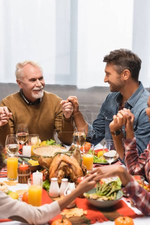 pleased multicultural family holding hands during dinner on thanksgiving holiday