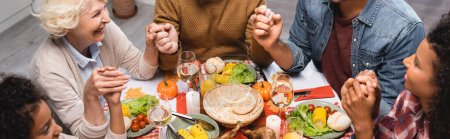 Panoramic crop of multiethnic family celebrating thanksgiving at home
