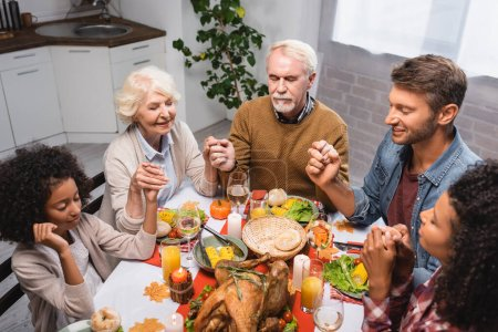 multiethnic family with closed eyes holding hands and celebrating thanksgiving at home