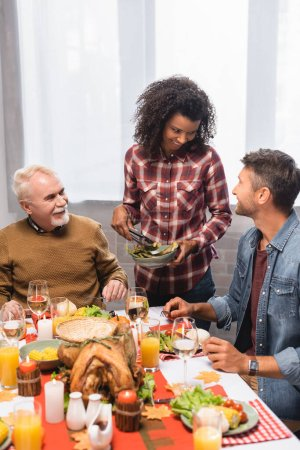 African american woman holding plate with asparagus and looking at man