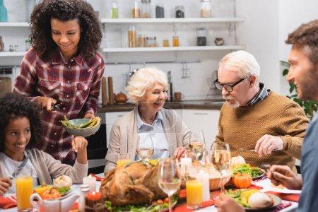 Photo pour Foyer sélectif de joyeuse femme afro-américaine servant des légumes pendant le dîner festif le jour de l'Action de grâces - image libre de droit