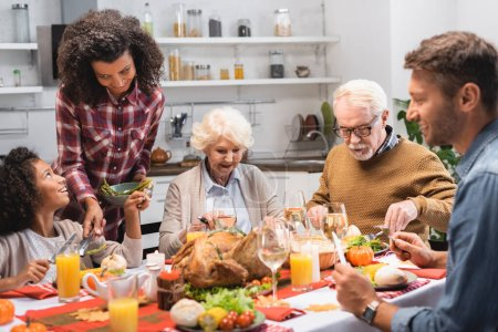 selective focus of african american woman serving vegetables during thanksgiving dinner with multicultural family