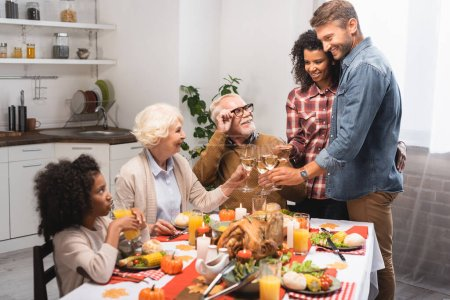 Photo for Excited multiethnic family clinking wine glasses while celebrating thanksgiving day - Royalty Free Image