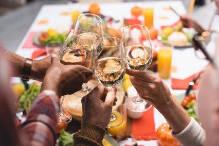 Photo pour Vue partielle de parents multiethniques clinquant des verres à vin tout en célébrant le jour de l'Action de grâce - image libre de droit