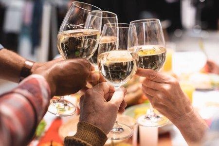 Photo pour Vue recadrée de parents multiculturels cliquetis verres à vin pendant le dîner de Thanksgiving - image libre de droit