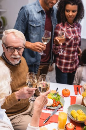 Selective focus of elderly woman clinking wine with man during thanksgiving celebration with multiethnic family