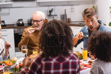 Selective focus of multiethnic family eating together during thanksgiving dinner