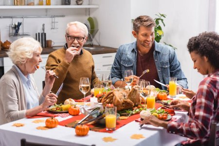 Selective focus of multicultural family with daughter celebrating thanksgiving near tasty food on table