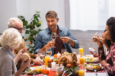 Selective focus of man holding wine near multiethnic family during thanksgiving ginner at home
