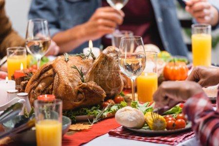 Ausgeschnittene Ansicht der Türkei mit Getränken und Kerzen auf dem Tisch in der Nähe multiethnischer Familie, die Erntedank feiert