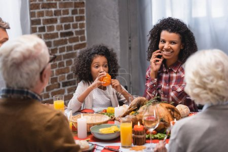 Selective focus of african american woman sitting near daughter and family while celebrating thanksgiving
