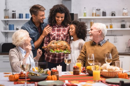 Selective focus of african american woman holding turkey near family during thanksgiving celebration