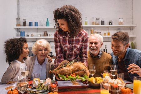 Selective focus of african american woman holding delicious turkey near family and decorations on table