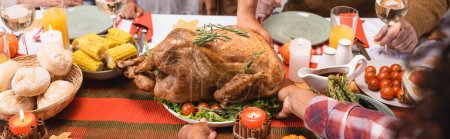 Photo for Horizontal image of african american woman putting turkey on table near family during thanksgiving dinner - Royalty Free Image