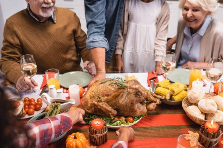 Selective focus of african american woman putting turkey on table near family and thanksgiving dinner