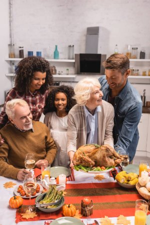 Selective focus of multiethnic family holding tasty turkey near candles on table