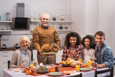 Concentration sélective de l'homme âgé tenant la dinde près de la famille multiethnique avec du vin pendant l'Action de grâces