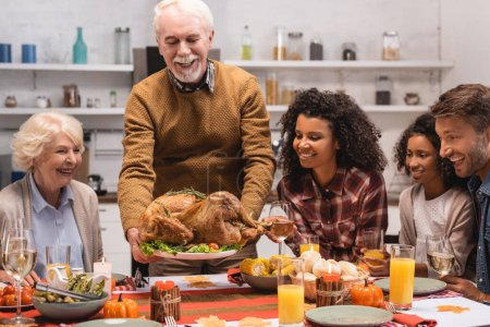 Photo for Selective focus of multiethnic family sitting near senior man with turkey in kitchen - Royalty Free Image