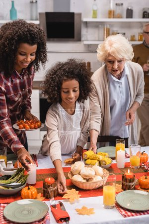 Selective focus of multiethnic women and african american girl serving thanksgiving dinner