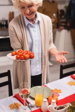 Selective focus of senior woman holding plate with cherry tomatoes during thanksgiving celebrations