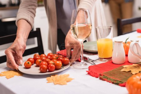 Cropped view of senior woman putting cherry tomatoes on table near autumn leaves and pumpkins