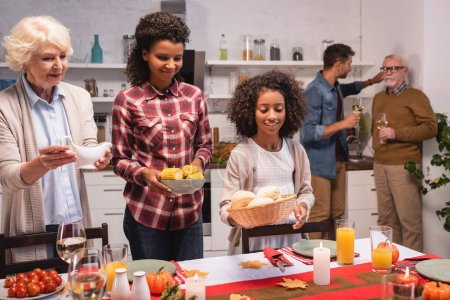 Selective focus of african american child holding buns near parents during thanksgiving dinner at home