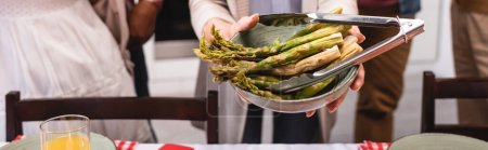 Photo for Horizontal image of elderly woman holding bowl of asparagus near multiethnic family during thanksgiving - Royalty Free Image