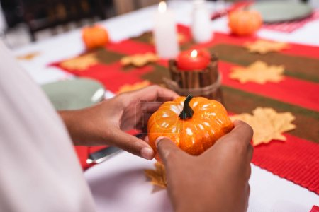 Cropped view of african american child holding decorative pumpkin during thanksgiving celebration