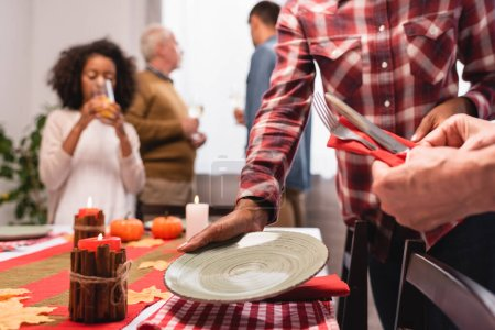 Selective focus of multiethnic women serving table during thanksgiving celebration
