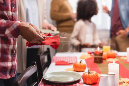 Selective focus of african american woman holding cutlery near decorations on table during thanksgiving celebration