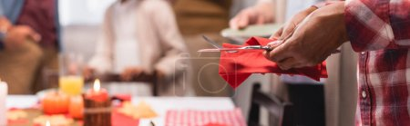 Photo for Panoramic shot of african american woman serving cutlery during thanksgiving celebration with family - Royalty Free Image
