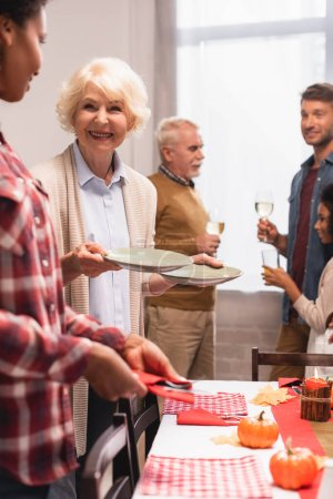 Photo for Selective focus of multiethnic family serving table during thanksgiving celebration at home - Royalty Free Image