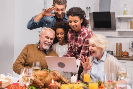 Photo for Selective focus of multicultural family having video call on laptop near food during thanksgiving - Royalty Free Image