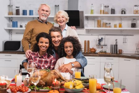 Photo for Selective focus of multicultural family hugging while celebrating thanksgiving at home - Royalty Free Image