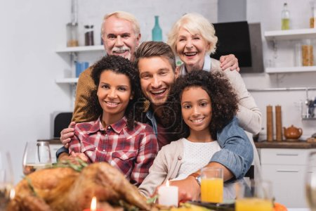 Photo for Selective focus of multicultural family looking at camera while celebrating thanksgiving - Royalty Free Image