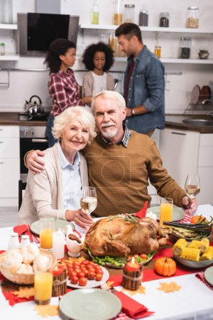 Selective focus of elderly man embracing woman while celebrating thanksgiving with multiethnic family