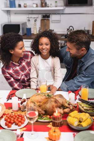 Selective focus of multiethnic parents looking at african american daughter during thanksgiving at home