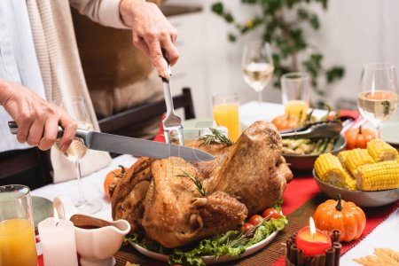 Cropped view of senior woman cutting turkey on table during thanksgiving celebration