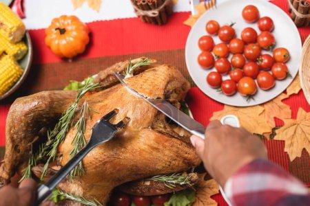 Photo pour Vue recadrée d'une femme afro-américaine avec fourchette et couteau coupant la dinde pendant le dîner d'Action de grâces - image libre de droit