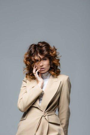 Photo pour Elegant woman in beige suit posing isolated on grey - image libre de droit