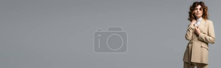 Photo pour Elegant woman in beige suit posing isolated on grey, panoramic shot - image libre de droit