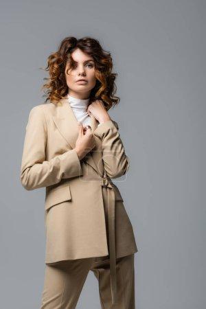 Photo pour Élégante femme en costume beige posant isolé sur gris - image libre de droit