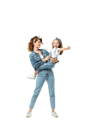 Photo for Mother and daughter in denim outfits having fun isolated on white - Royalty Free Image