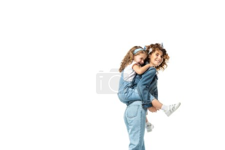 Photo for Side view of mother piggybacking daughter in denim outfit isolated on white - Royalty Free Image