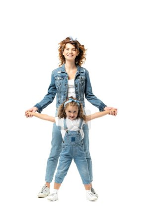 Photo for Mother and daughter in denim outfits posing and smiling isolated on white - Royalty Free Image