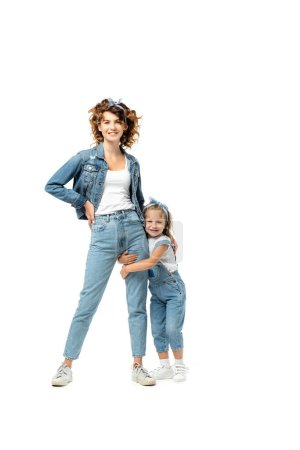 daughter in denim outfit hugging mother leg isolated on white