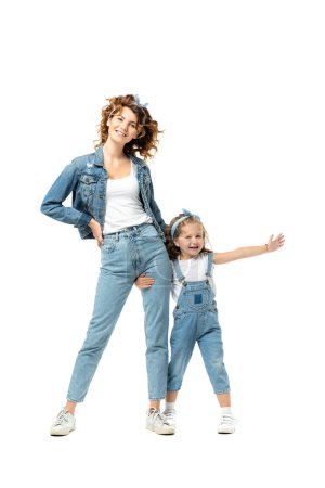 daughter in denim outfit hugging mother leg with outstretched hand isolated on white